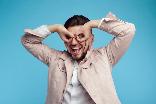 Joyeux jeune homme s'amusant en studio posant sur fond bleu