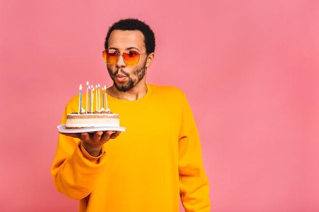 Joyeux jeune homme soufflant des bougies sur un gâteau d'anniversaire isolé sur rose.