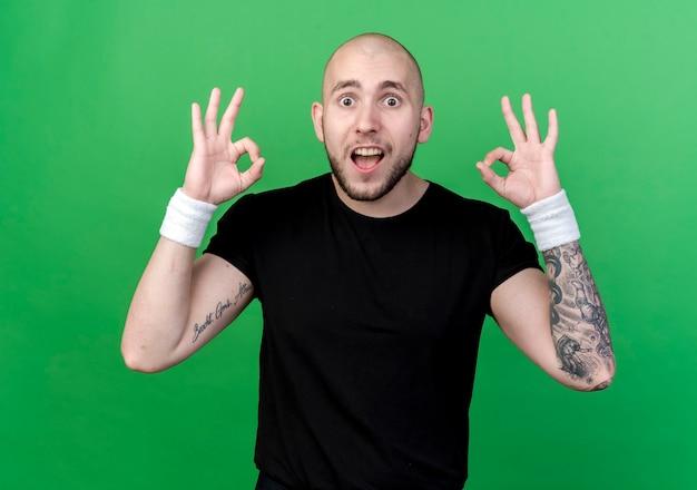 Joyeux jeune homme sportif portant un bracelet montrant le geste okey isolé sur mur vert