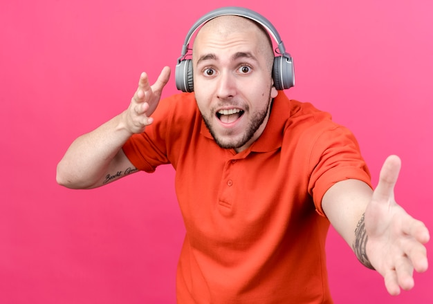 Joyeux jeune homme sportif portant des écouteurs et tenant la main isolée sur un mur rose