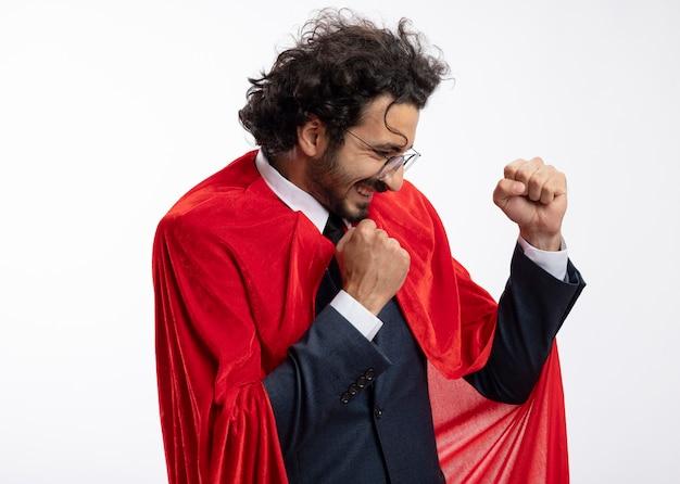 Joyeux jeune homme de super-héros dans des lunettes optiques portant costume avec manteau rouge se tient sur le côté en gardant les poings isolés sur un mur blanc