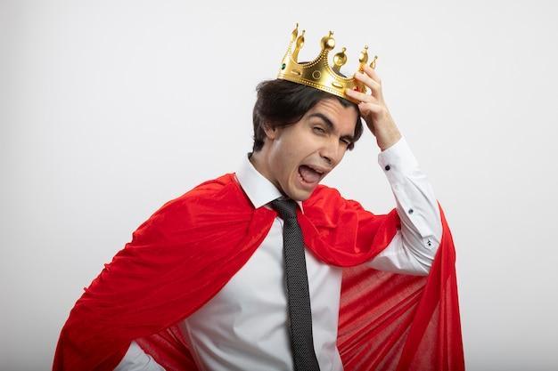 Joyeux jeune homme de super-héros portant une cravate mettant la couronne sur la tête isolé sur fond blanc