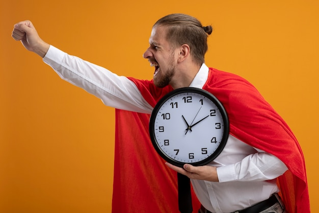 Joyeux jeune homme de super-héros portant une cravate tenant une horloge murale et levant le poing isolé sur orange