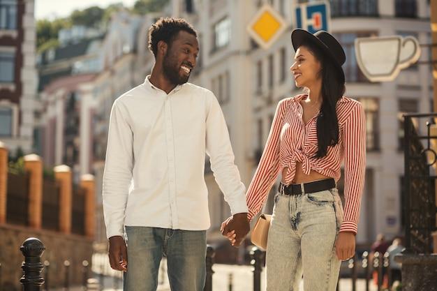 Joyeux jeune homme tenant la main de sa belle petite amie à l'extérieur et riant