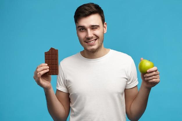 Joyeux jeune mec brune caucasienne en t-shirt blanc fait un mauvais choix