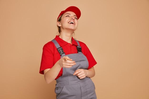 Joyeux jeune ouvrier du bâtiment portant l'uniforme et une casquette en regardant la caméra en riant
