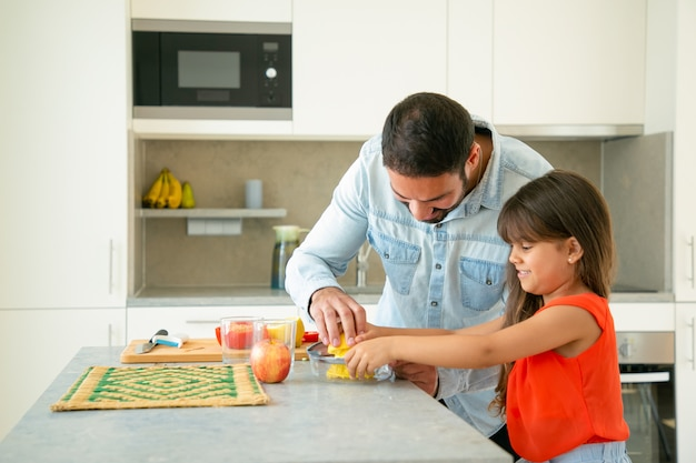Joyeux jeune papa et sa fille appréciant la cuisine ensemble. fille et son père pressant du jus de citron au comptoir de la cuisine. concept de cuisine familiale