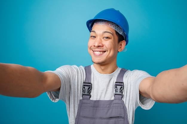 Joyeux jeune travailleur de la construction portant un casque de sécurité et l'uniforme s'étendant les mains vers la caméra