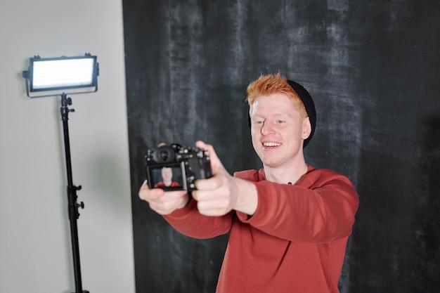 Joyeux jeune vlogger en tenue décontractée debout sur fond noir et tenant la caméra devant lui