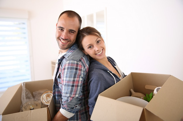 Joyeux jeunes adultes emballant leurs affaires dans des cartons