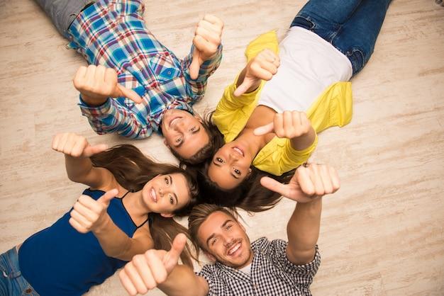 Joyeux jeunes allongés sur le sol montrant les pouces vers le haut