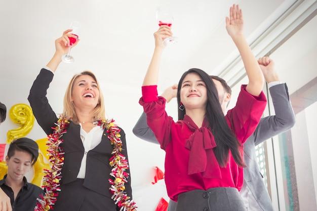 Joyeux jeunes célébrant la tenue des flûtes de champagne.