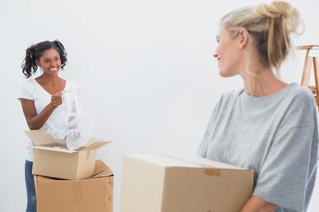 Joyeux jeunes colocataires emménageant dans une nouvelle maison et déballant des boîtes