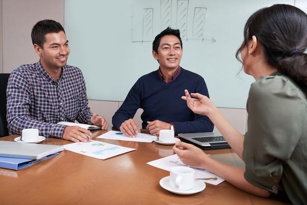 Joyeux jeunes gens d'affaires ayant une séance de brainstorming