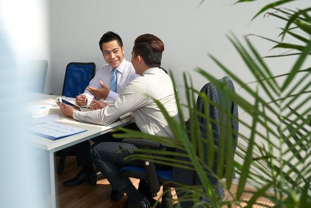 Joyeux jeunes hommes d'affaires planifiant des travaux lors de la réunion