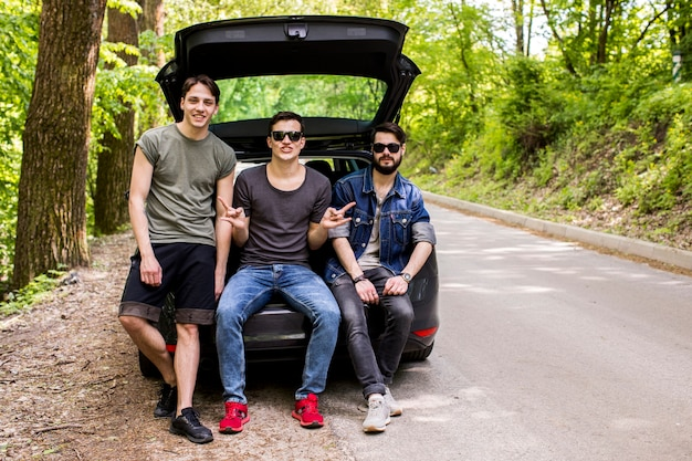 Joyeux jeunes mecs assis dans le coffre sur la route forestière