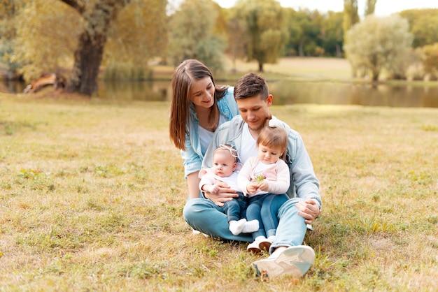 Joyeux jeunes parents ayant du temps avec leurs enfants en plein air dans la nature au coucher du soleil
