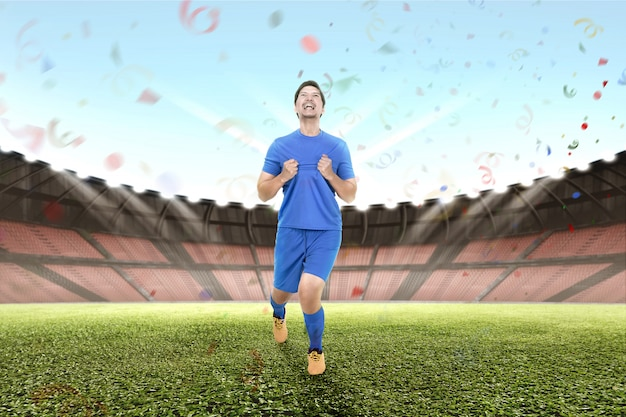 Joyeux joueur de football asiatique masculin célébrer
