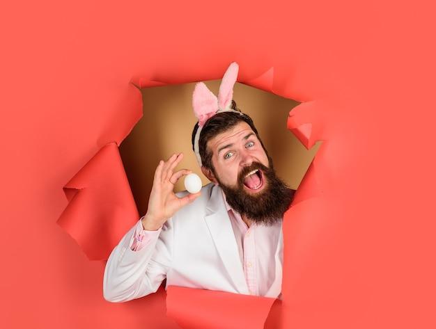 Joyeux jour de pâques homme barbu avec des oreilles de lapin homme souriant tient un oeuf blanc barbu à travers du papier
