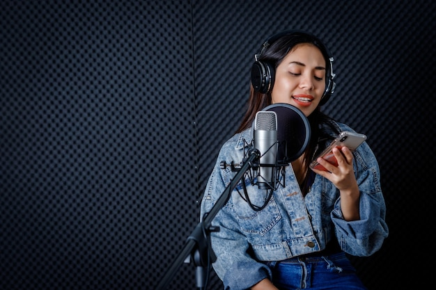 Joyeux joyeux assez souriant du portrait d'une jeune femme asiatique regarde le chanteur du smartphone portant des écouteurs enregistrant une chanson devant le microphone dans un studio professionnel