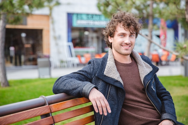 Joyeux joyeux contenu joyeux jeune homme bouclé en veste noire assis et se reposant sur le banc dans le parc