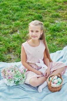 Joyeux lapin de pâques. enfant s'amusant en plein air. enfant jouant avec des oeufs et du lapin sur l'herbe verte.
