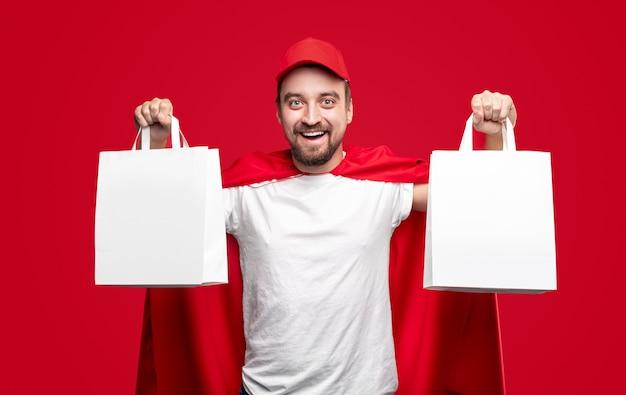 Joyeux livreur barbu en bonnet rouge et cape de super-héros démontrant des sacs en papier blanc vierge tout en représentant un service rapide pour la livraison de nourriture