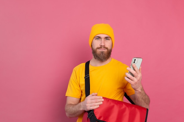 Joyeux livreur européen avec sac casual hold phone on pink