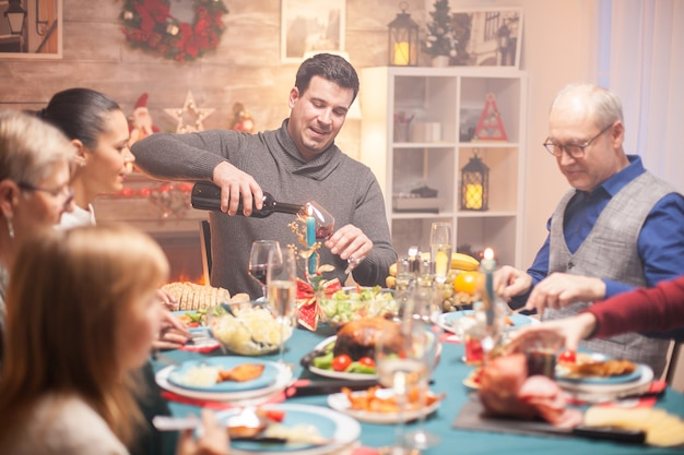 Joyeux mari versant du vin rouge dans un verre au dîner de noël en famille.