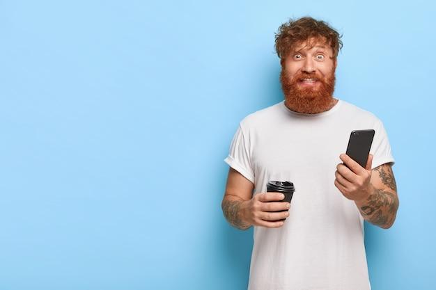Joyeux mec aux cheveux rouges posant avec son téléphone