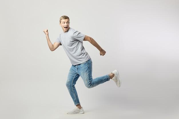 Joyeux mec blond vêtu d'un t-shirt blanc et d'un jean s'exécutant joyeusement sur fond blanc