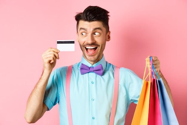 Joyeux mec drôle regardant la carte de crédit en plastique et souriant, acheter des cadeaux, tenant des sacs à provisions, debout sur fond rose.