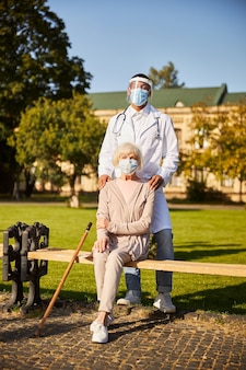 Joyeux médecin afro-américain dans une robe d'hôpital blanche avec un stéthoscope autour du cou touchant les épaules d'une vieille femme