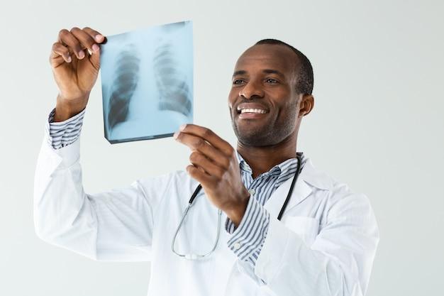 Joyeux médecin professionnel souriant analysant le balayage w-ray contre le mur blanc