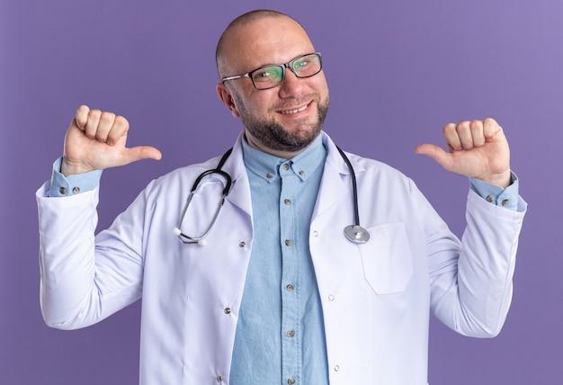 Joyeux médecin de sexe masculin d'âge moyen portant une robe médicale et un stéthoscope avec des lunettes pointant sur lui-même isolé sur un mur violet