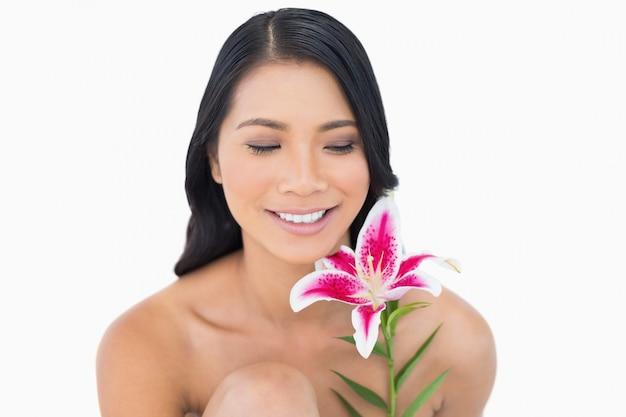Joyeux modèle aux cheveux noirs naturel posant avec lis