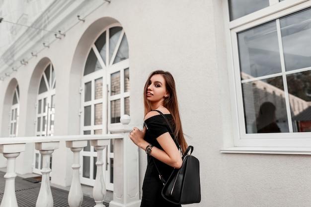 Joyeux modèle de belle jeune femme dans une élégante robe noire avec un élégant sac à dos en cuir noir parcourt la ville. heureuse fille à la mode bénéficie d'une promenade dans une rue. mode jeunesse de rue.