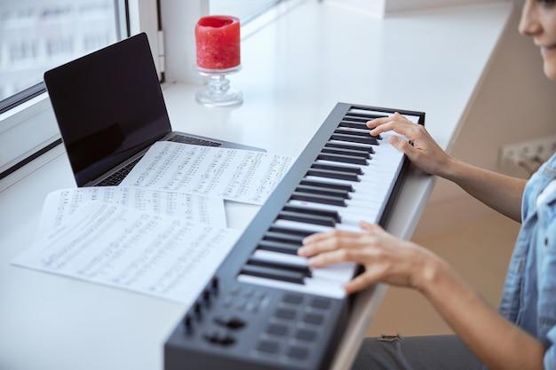 Joyeux musicien exprimant sa positivité tout en apprenant une nouvelle mélodie à partir de notes