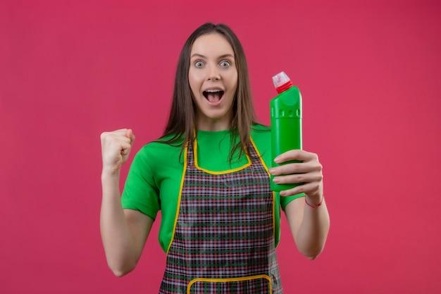 Joyeux nettoyage jeune femme en uniforme tenant un agent de nettoyage montrant oui geste sur mur rose isolé