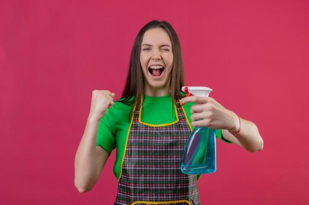 Joyeux nettoyage jeune femme en uniforme tenant spray de nettoyage montrant oui geste sur mur rose isolé