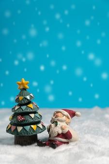 Joyeux noël avec boîte de cadeaux, assis sur la neige près de l'arbre de noël.