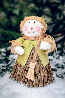 Joyeux noël bonhomme de neige fait maison avec balai et sourit dans la neige