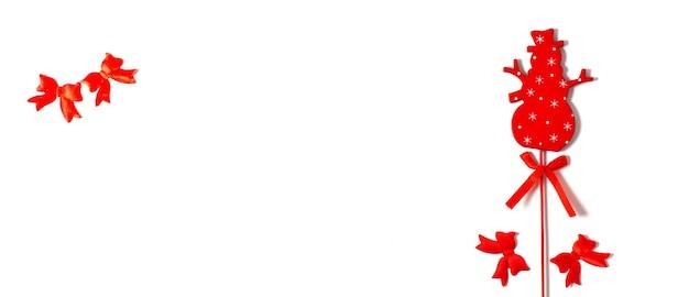 Joyeux noël. bonhomme de neige rouge avec des arcs sur fond blanc, bonne année, mise à plat, bannière