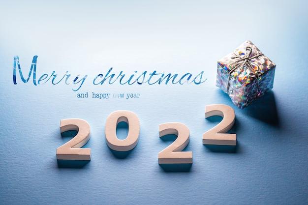 Joyeux noël et bonne année 2022 avec un cadeaucarte postale avec boîte cadeau de noëlnuméros 2022
