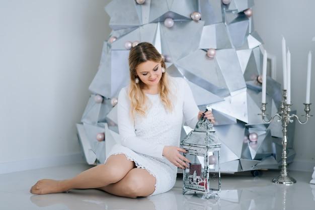Joyeux noel et bonne année. belle fille assise avec un chandelier près de l'arbre de noël en métal argenté moderne