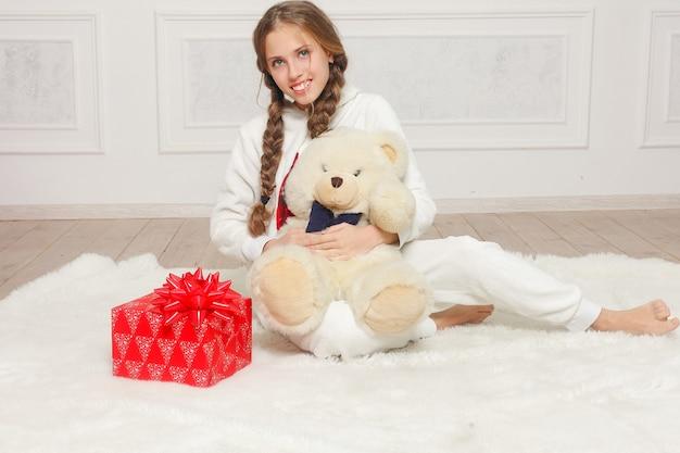 Joyeux noël et bonne année belle fille enfant heureuse en pyjama en attente d'un miracle à la maison avec arbre de noël. petite fille souriante avec boîte-cadeau de noël. concept de vacances et de personnes.