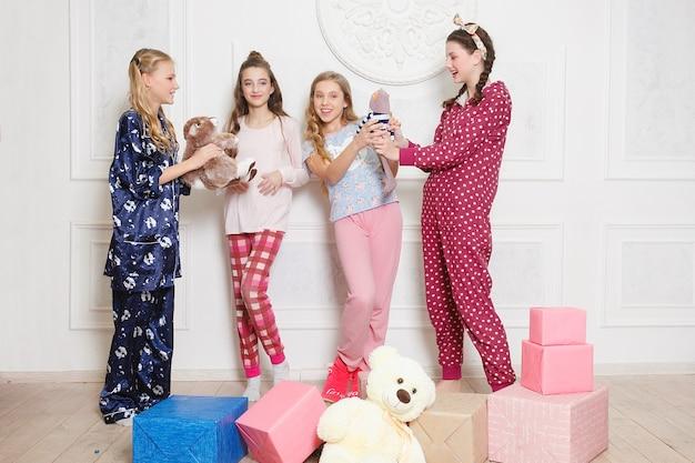 Joyeux noël et bonne année belle fille heureuse de quatre enfants en pyjama en attente d'un miracle à la maison avec arbre de noël. petite fille souriante avec boîte-cadeau de noël. vacances, concept de personnes.