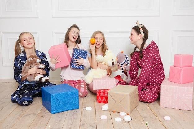Joyeux noël et bonne année belle fille heureuse de quatre enfants en pyjama en attente d'un miracle à la maison avec un arbre de noël. petite fille souriante avec boîte-cadeau de noël. vacances, concept de personnes.
