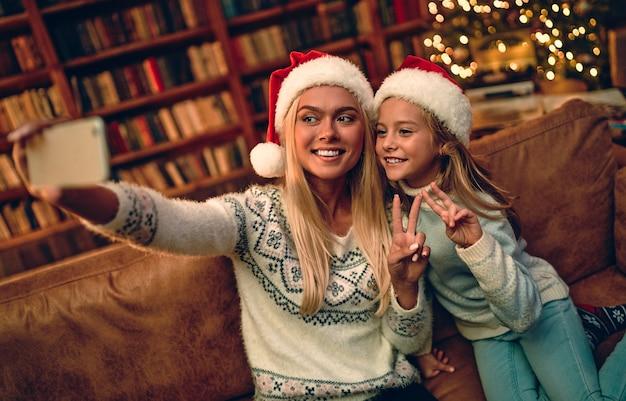Joyeux noel et bonne année! belle maman et sa fille en chapeaux de père noël font un selfie à l'aide d'un téléphone intelligent et sourient tout en célébrant.
