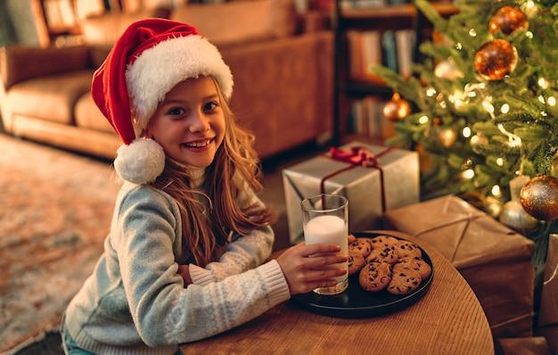 Joyeux noel et bonne année! charmante petite fille préparée pour le père noël un verre de lait et des biscuits.